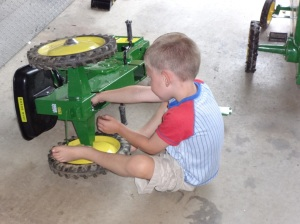 Kid fixing pedal tractor